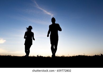 A silhouette of a jogger couple in sunrise