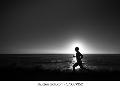 A silhouette of jogger at a grassy path along the ocean.  In black and white.