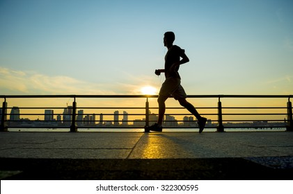 Silhouette of jogger running at sunset in front of the city skyline