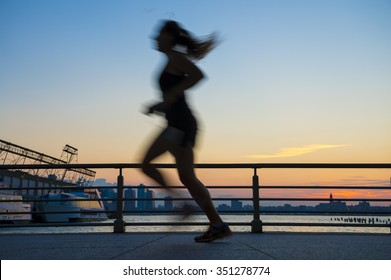 Silhouette of jogger running at sunset in front of the city skyline on the West Side in New York City