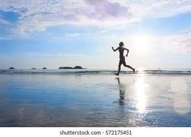 Silhouette of jogging woman at sunset or sunrise wet beach with beautiful reflection on sand. Healthy lifestyle, fitness concept.