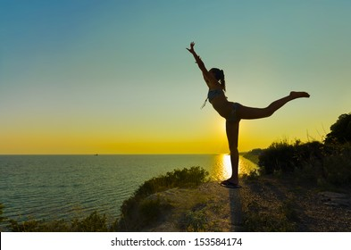 Silhouette of Joy. Silhouette of a gymnast backlit girl in balance on a beam at sunset against sea horizon