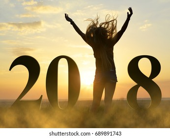 Silhouette the joyful girl with arms over her head in celebration of the New Year 2018.