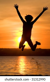 Silhouette of joyful guy jumping with raised arms near lake at sunset