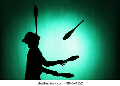 silhouette of a juggler with sticks on a blue background