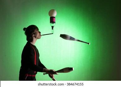 silhouette of a juggler with sticks on a green background