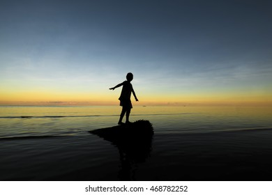Silhouette of jumping group kid, people stand on beach during sunset with warm tone