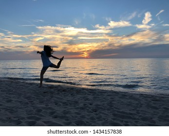 Silhouette jumping for joy during the sunset at Lake Michigan in the summer.