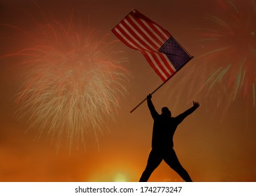 silhouette of jumping patriot girl holding the american flag on the 4th of July. Patriotic holiday. Happy young man with American flag looking at fireworks. USA celebrate 4th of July.