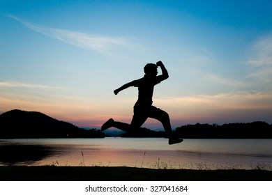 Silhouette jumping in sunset sky.