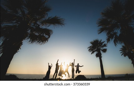 silhouette jumping team of people at the sea on a sunset background