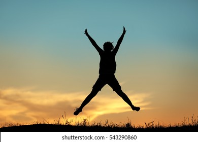 Silhouette of jumping woman on sunset sky background
