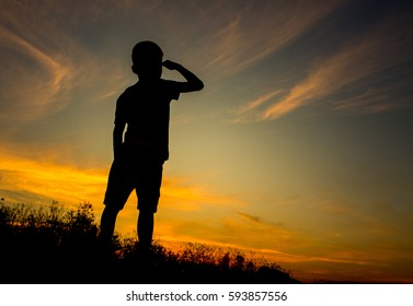 Silhouette of kid looking something at the sky and the beautiful sky in the evening