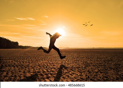 Silhouette of kid running on beach at sunset