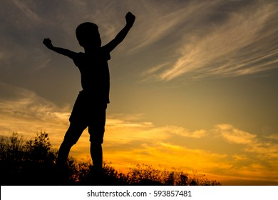 Silhouette of kid stretch the arms and the beautiful sky in the evening