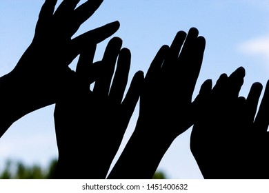 Silhouette of kids hands reaching up to the sky, against the light blue sky of summer in Madison, Wisconsin.