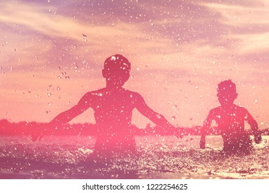 Silhouette of kids having fun and splashing in the sea. Summer vacation and healthy lifestyle concept.