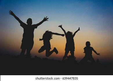 silhouette of kids running and enjoy in midst of rice field at sunset