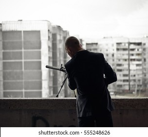 Silhouette of killer or hitman with weapons at day. shot, holding rifle, sniper rifle, blurred building background