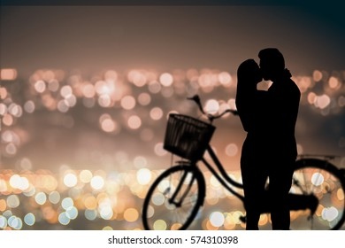Silhouette of kissing couple love on the cit light bokeh