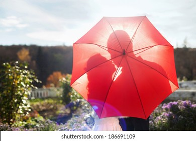 Silhouette of kissing couple under umbrella