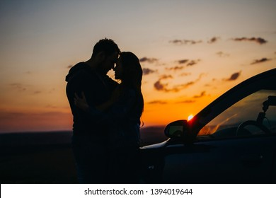 Silhouette kissing men and women at sunset in the car. A couple in love travels by car at sunset.