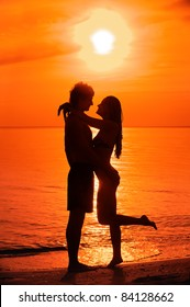 Silhouette of kissing young couple against sea sunset.