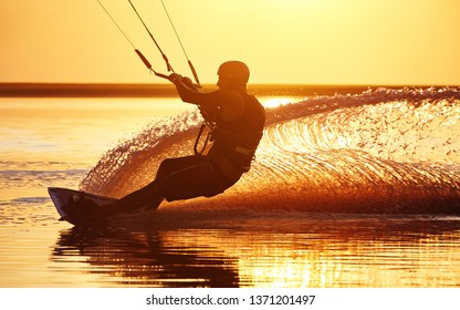 Silhouette of a kitesurfer during a trick on a board with water splashes