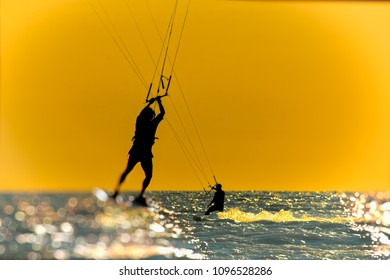 Silhouette of kitesurfer, jumping over the sea on sunset sky background. Photo toned