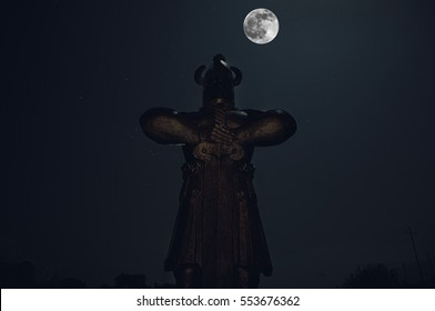 silhouette of knight monument with sword at night and big bright moon at the sky, Celtic landscape
