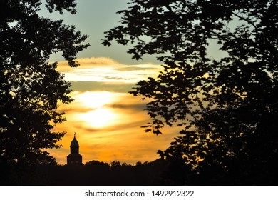 The silhouette of the Kokuy tower - part of the Novgorod Kremlin through the foliage at sunset. Veliky Novgorod, Russia