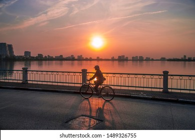 Silhouette of a lady riding a bicycle by a lake in an urban area with the sunset in the background. Shot in Hanoi, Vietnam.