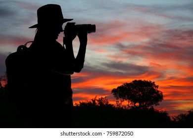 Silhouette of  Lady in Safari Dress taking Photographs at Sunset in Africa