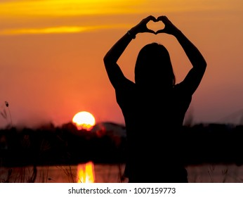 Silhouette of Lady showing heart shaped hands in sunrise background. Valentine day concept