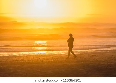 Silhouette of lady walking on the beach at sunset