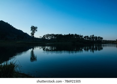 Silhouette, landscape water reflection of sunset and sky at lake in evening with mountain background, Chiangdao countryside, Thailand.