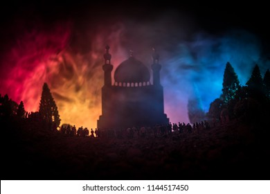 Silhouette of a large crowd of people in forest at night standing against a blurred mosque building with toned light beams on foggy background. Ramadan Kareem background. Praying people concept.