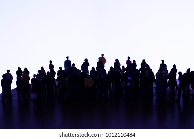 Silhouette of a large group of unrecognizable people. High contrast mob, squad, or crew of men and women. Big crowd or team on white with space for text. High contrast miniature photo.