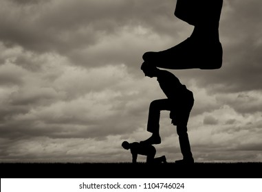 Silhouette of a large leg presses on a man who also presses his foot on another man lying on the ground. The concept of manipulation and control over people