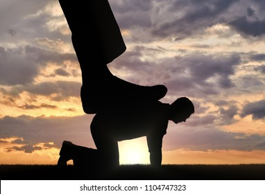 Silhouette of a large leg pressing on a man who fell on all fours. The concept of humiliation of human dignity