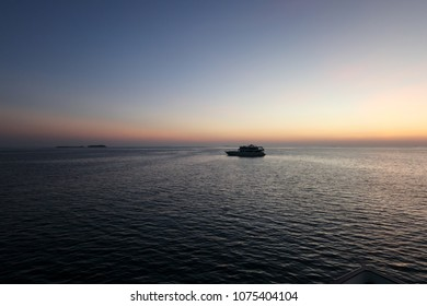 Silhouette of large yacht on ocean at sunset with pacific island in background
