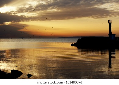 Silhouette of a lighthouse on a brick wall in a sunset with dark clouds and the sky and the sea in gold