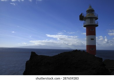silhouette lighthouse in Punta de Teno, on the Canary Island of Tenerife, giant moles of volcanic rock ending in the Atlantic Ocean, from blue waters are common whale sightings