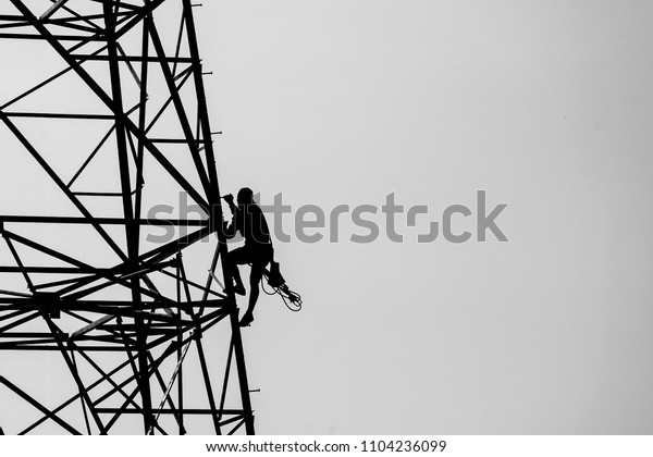 Silhouette Lineman Climbing On Transmission Line Industrial Stock Image 1104236099