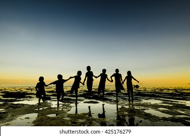 Silhouette of lineup group of kid, people stand on beach with water reflection