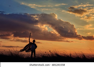 Silhouette of little boy hold toy sword playing on sunset