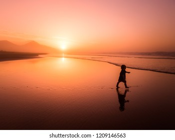 Silhouette of little boy running on Cofete beach in Fuerteventura, Canary Islands.