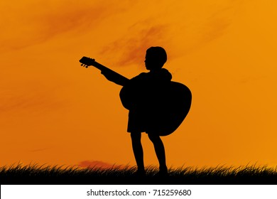 Silhouette a little boy traveling with guitar. Summer, Asian kid at the sunset, happy time, Children who have dreams of being a musician.