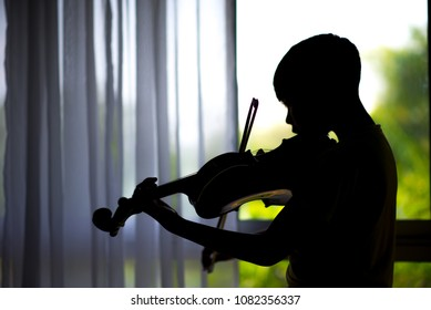 silhouette Little boys play and practice violin in the music class room