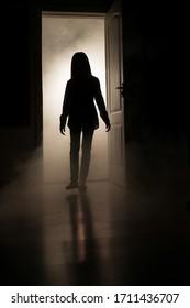 Eine Silhouette eines kleinen Mädchens entsteht aus einem hellen Raum mit Rauch im Dunkeln. Das Konzept der Ängste und Mystik der Kinder.